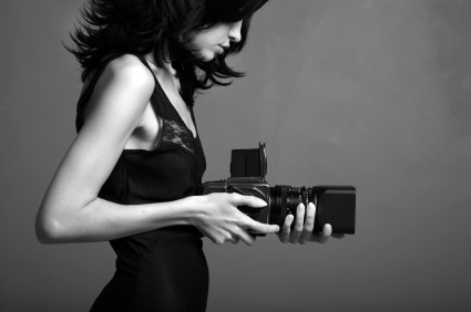 Fashion portrait of young photographing lady. Black and white photo